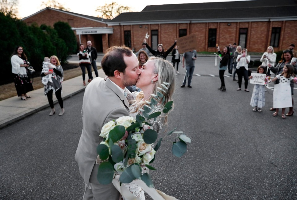 <strong>Newlyweds Holly Whittle and John Steinert kiss in front of their cheering friends who surprised them in the parking lot after their wedding on Saturday, March 21, 2020 at St. Louis Catholic Church. The couple had to pare down their wedding after social distancing was strongly encouraged to decrease the spread of the coronavirus.</strong> (Mark Weber/Daily Memphian)