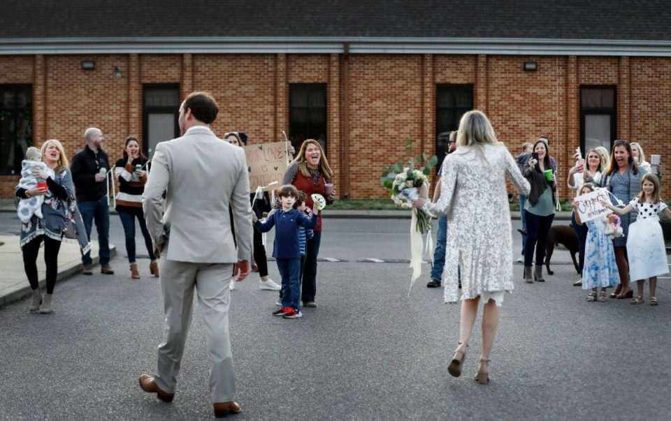 <strong>Newlyweds Holly Whittle and John Steinert celebrate with cheering friends who surprised them in the parking lot after their wedding on Saturday, March 21, 2020, at St. Louis Catholic Church.</strong> (Mark Weber/Daily Memphian)