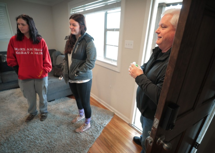 <strong>Armed with a bottle of hand sanitizer, Realtor Brad Vaughan (right) greets a family at his open house listing on Mesquite Road in East Memphis on Saturday, March 21.</strong>&nbsp;(Jim Weber/Daily Memphian)