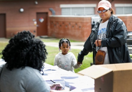 <strong>Sylvia Stewart and her 4-year-old granddaughter, Arianna Moore, pick up instructional learning packets during a Shelby County Schools food-distribution event Monday, March 23, at Orange Mound Community Center.</strong> (Mark Weber/Daily Memphian)