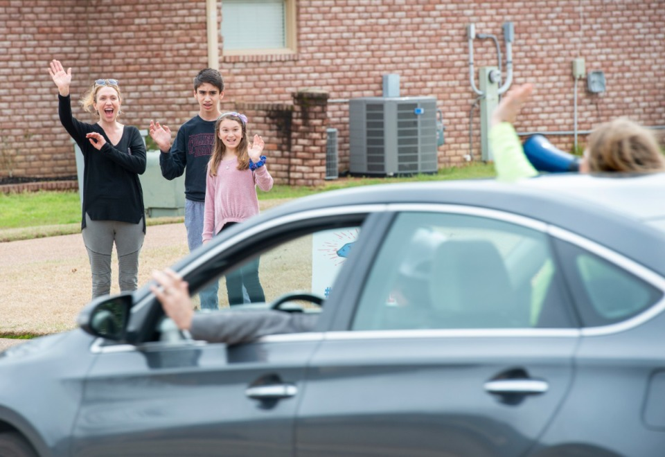<strong>Doriann Fairchild and her son, Cole, and daughter Brielle wave at the teachers and administration of Bailey Station Elementary School as they pass through their neighborhood in Collierville Monday, March 23, 2020.</strong> (Greg Campbell/Special to The Daily Memphian)