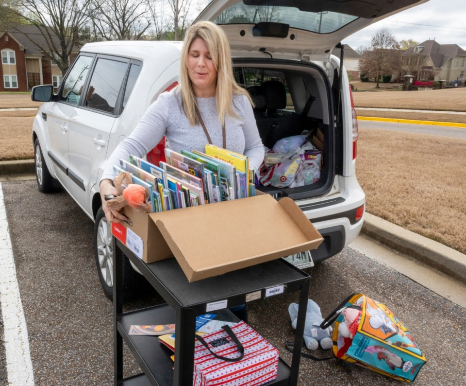 <strong>Bailey Station Elementary School librarian Jennifer Boren takes home stacks of books from the school for virtual story time with the students of the school. The teachers and administration of the school gathered for a caravan through the neighborhoods of their students Monday, March 23, 2020.</strong> (Greg Campbell/Special to The Daily Memphian)