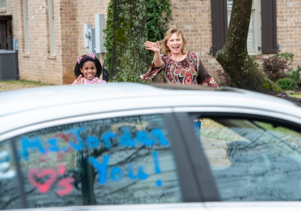 <strong>L'cee Wallace, fourth grader at Bailey Station Elementary School and her mother Martha Tisdale wave at the teacher caravan through their Collierville neighborhood Monday, March 23, 2020. The teachers and administration drove a caravan through all the neighborhoods of the students of the shool to help with moral, both the teachers and students.</strong> (Greg Campbell/Special to The Daily Memphian)