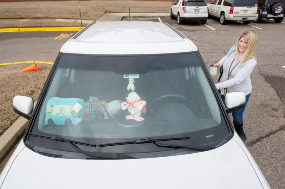 <strong>Bailey Station Elementary School librarian Jennifer Boran gets ready for the caravan through the neighborhoods of the students of the school Monday, March 23, 2020. Boran put some stuffed figures from the student's favorite books in her dashboard for the caravan.</strong>(Greg Campbell/Special to The Daily Memphian)