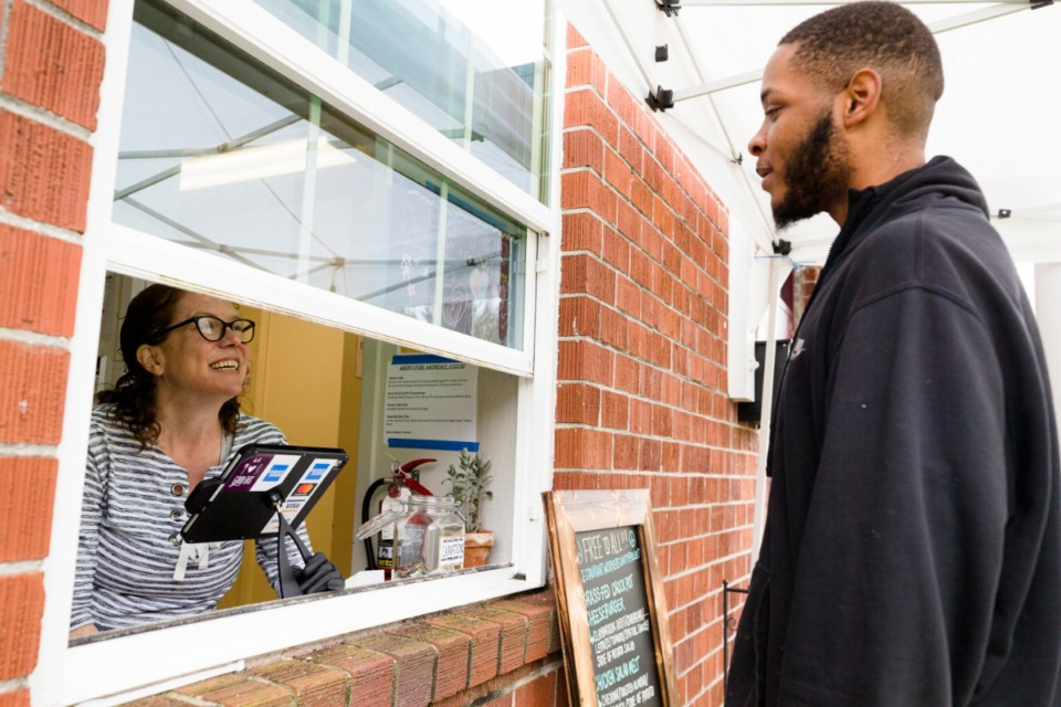 <strong>Caritas Volunteer Emmy Miller takes an order from Brodrick Peete in Midtown on March 23, 2020.</strong> (Ziggy Tucker/Daily Memphian)