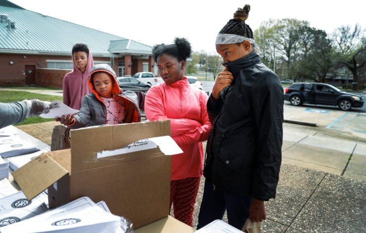 <strong>Students (left to right) Traevone Toney, 12, Zaniya Toney, 8, Janae Fisher, 10, and Kelsey Porter, 12, pick up work packets during a Shelby County Schools food distribution event Monday, March 23, 2020, at Orange Mound Community Center.</strong> (Mark Weber/Daily Memphian)
