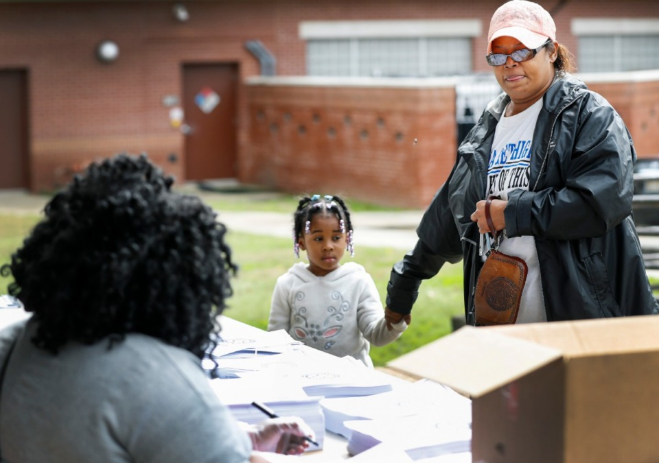 <strong>Sylvia Stewart (right) along with granddaughter Arianna Moore, 4, grab work packets during a Shelby County Schools food distribution event Monday, March 23, 2020 at Orange Mound Community Center.</strong> (Mark Weber/Daily Memphian)