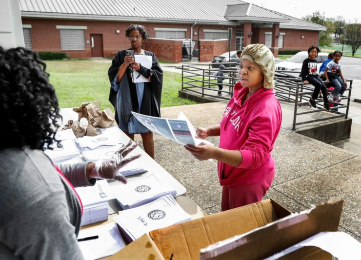 <strong>Parent Dasha Pullen (right) grabs work packet for her children during a Shelby County Schools food distribution event Monday, March 23, 2020 at Orange Mound Community Center.</strong> (Mark Weber/Daily Memphian)