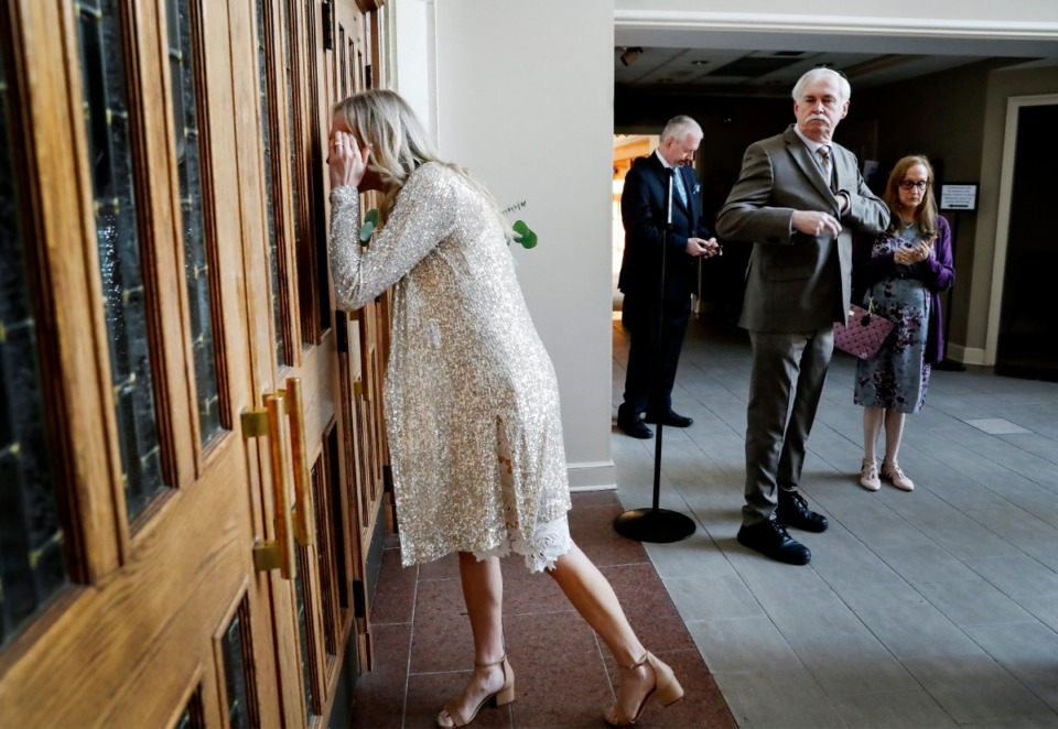 <strong>Bride Holly Whittle (left) looks through a door before her wedding to John Steinert on Saturday, March 21, 2020, at St. Louis Catholic Church. The couple had to pare down their wedding after social distancing was strongly encouraged to decrease the spread of the coronavirus.</strong> (Mark Weber/Daily Memphian)