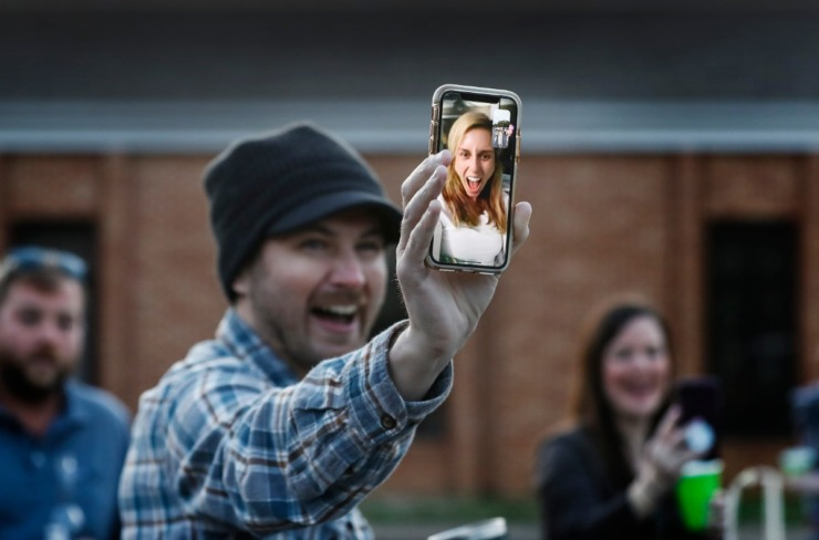 <strong>Logan Abrahams hold a smart phone of a screaming Kristin Barry while they FaceTime during a surprise party for couple Holly Whittle and John Steinert after the couple married on Saturday, March 21, 2020, at St. Louis Catholic Church.</strong> (Mark Weber/Daily Memphian)