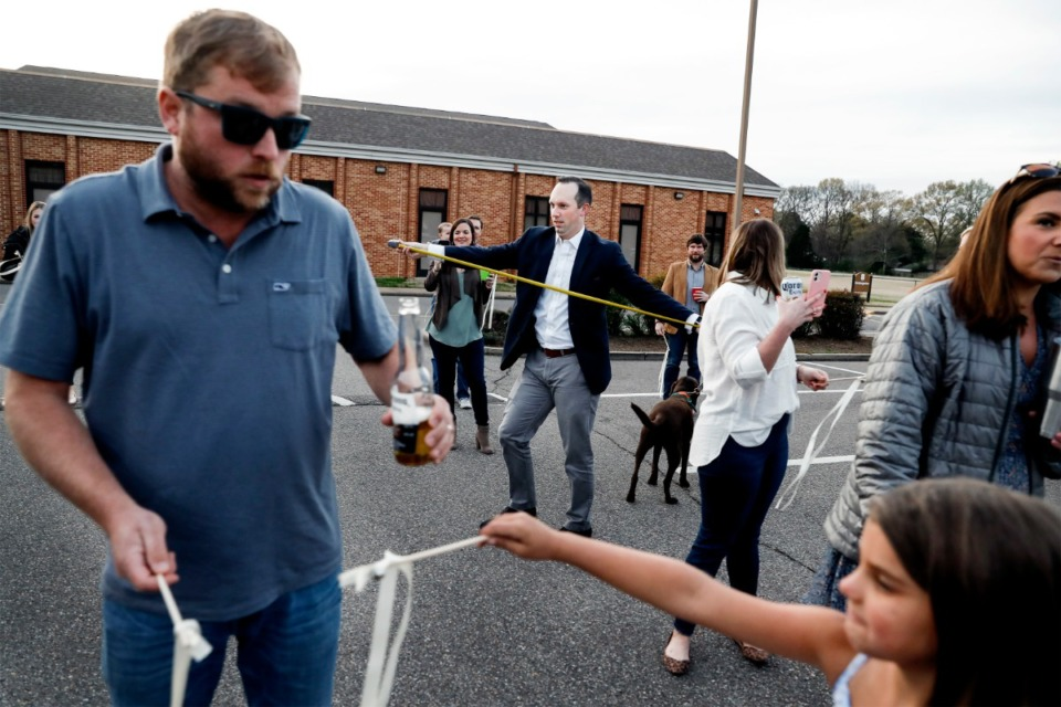<strong>Lance Horner (middle) uses a tape measure to make sure friends are six feet apart before they surprise bridal couple Holly Whittle and John Steinert after their wedding on Saturday, March 21, 2020, at St. Louis Catholic Church.</strong> (Mark Weber/Daily Memphian)