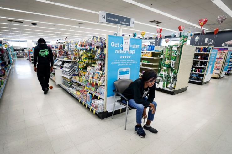 <strong>Dinishia Jones (right) sits by herself as her son Therron Farsee Jr. walks the Walgreens aisles on March 24, 2020, while they wait more than an hour for her prescriptions to be filled. Jones recently had surgery on her foot after stepping on a piece of glass while working as a server job at a&nbsp; Beale Street restaurant.</strong> (Mark Weber/Daily Memphian)