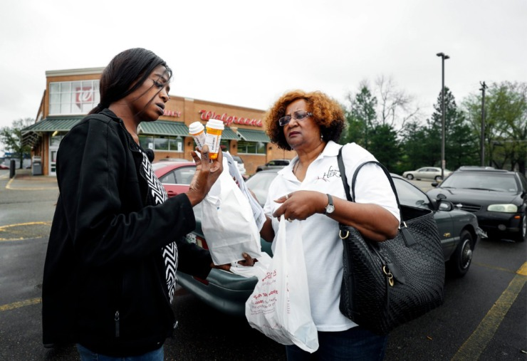 <strong>Dinishia Jones (left) checks to make sure she received all her prescriptions with Rev. Dr. Elaine Sanford in the Walgreens parking lot on Tuesday, March 24, 2020. HER Faith Ministries help Jones obtain her medicines that cost over $300.</strong> (Mark Weber/Daily Memphian)
