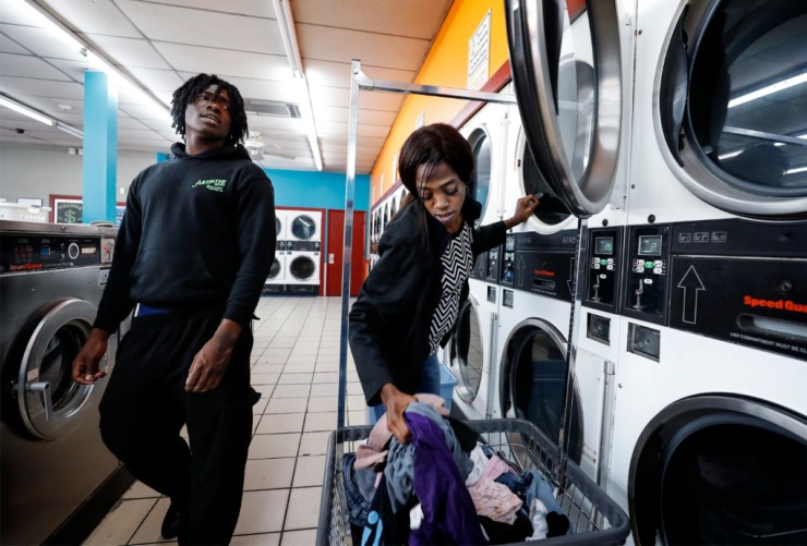 <strong>Dinishia Jones loads wet clothes into a dryer as son Therron Farsee, Jr., (left) hovers close by at a local laundromat on Tuesday, March 24, 2020.</strong> (Mark Weber/Daily Memphian)
