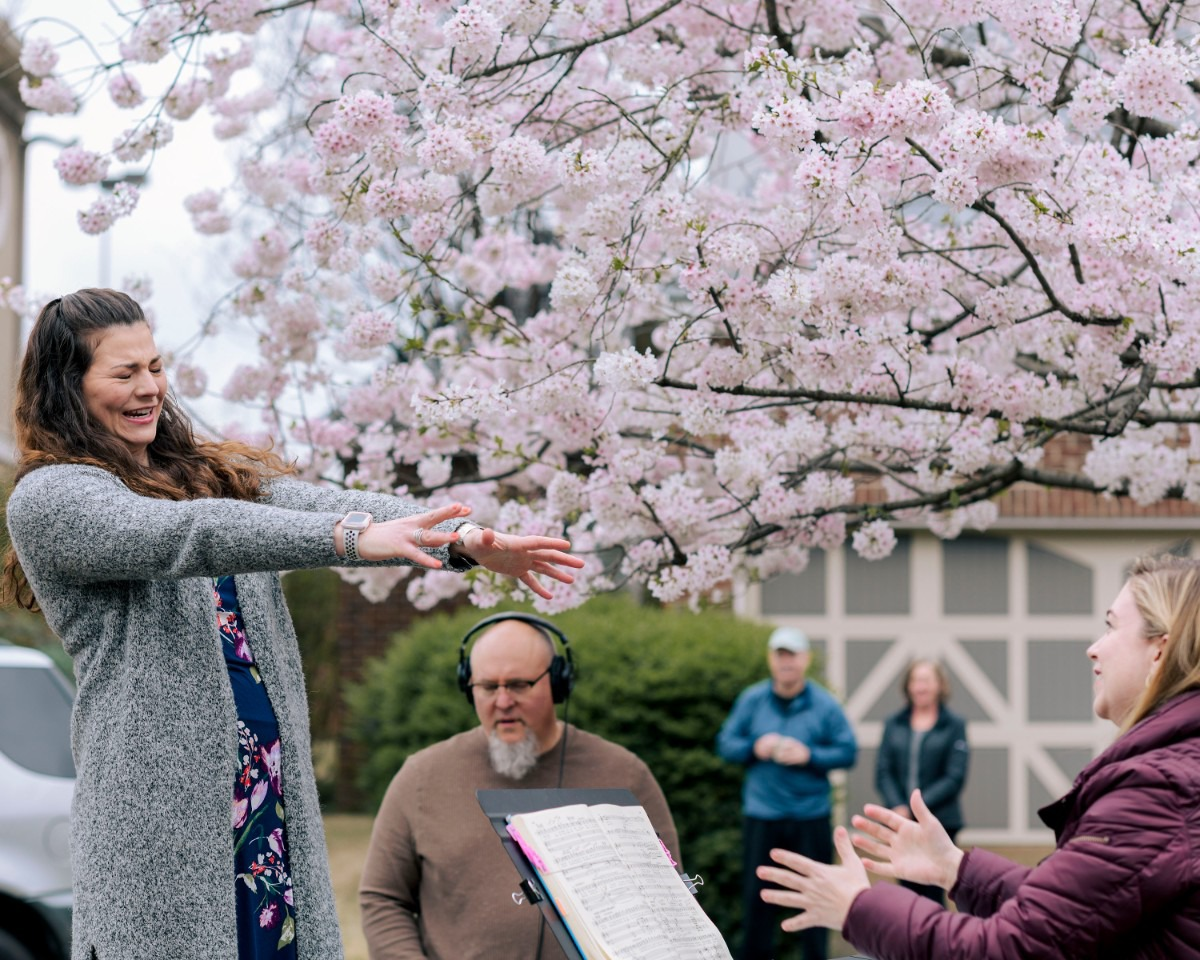 <strong>Helen Hassinger reaches out to grab her colleagues' hands before remembering she should avoid unnecessary contact to deter the spread of COVID-19. Hassinger and her Opera Memphis colleagues performed on lawns around Memphis.</strong> (Houston Cofield/Special to The Daily Memphian)