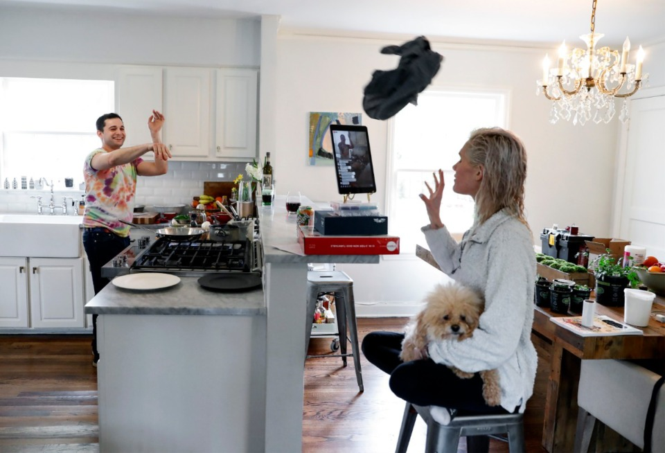 <strong>Chef Josh Steiner (left) throws his shirt to fiancee Wallis Tosi as she monitors questions while holding their pet dog Quinn during an online cooking club live on Facebook from their kitchen on Wednesday, March 25, 2020.</strong> (Mark Weber/Daily Memphian)