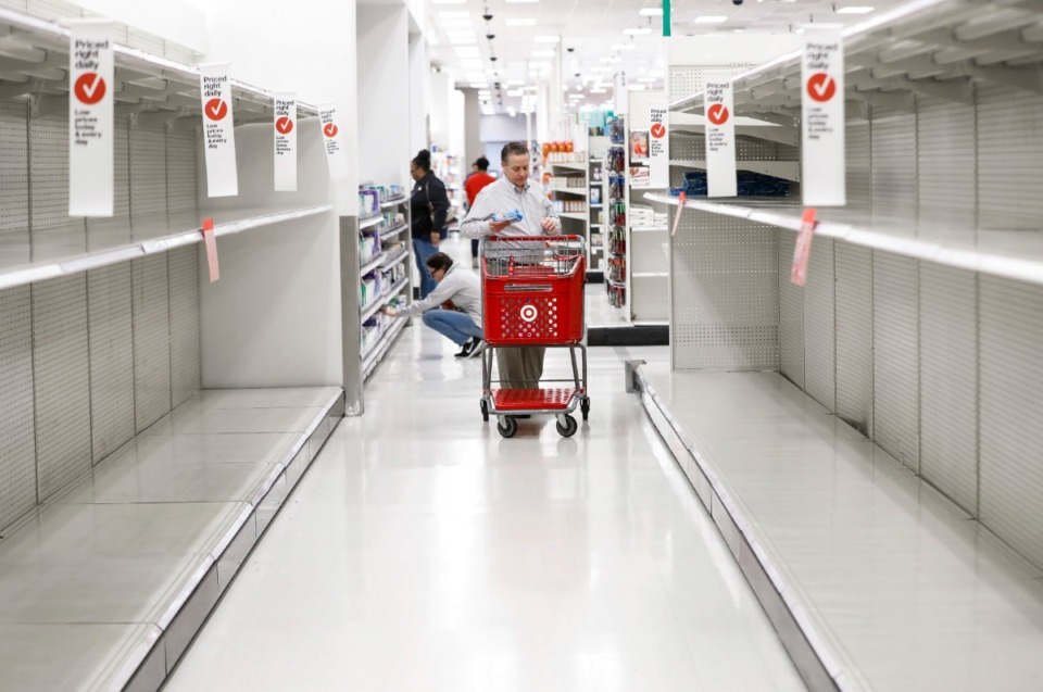 <strong>Customers shop among the empty paper goods aisle at the Target Memphis Central Store on Wednesday, March 18.</strong> <strong>With shelves cleaned out of toilet paper, paper towels, bread, sanitizer, beans, rice, pasta and frozen prepared foods in some stores, grocers said they have every confidence supplies will rebound, but it could take weeks to months.</strong> (Mark Weber/Daily Memphian)