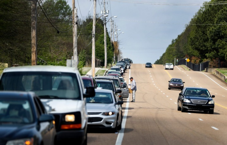 <strong>Memphis Athletic Ministries volunteer Jeff Cage (middle) directs traffic during a drive-through food distribution event on Friday, March 27, 2020. Cars backed up for over a mile, as they waited to grab supplies and food.</strong> (Mark Weber/Daily Memphian)