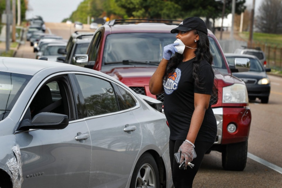 <strong>Memphis Athletic Ministries volunteer Kennyatta Morris (right) directs traffic during a drive-through food distribution event on Friday, March 27, 2020. Cars backed up for over a mile, as they waited to grab supplies and food.</strong> (Mark Weber/Daily Memphian)