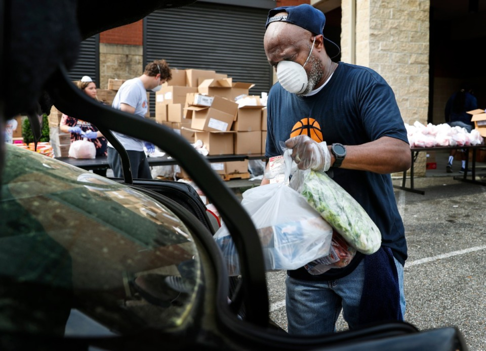 <strong>Memphis Athletic Ministries volunteer Lindell Bonner places fresh vegetables and fruit in a car trunk during a drive-through food distribution at a on Friday, March 27, 2020. The during the event nearly 12,000 pounds of food and 200 14- day food boxes where handed out to families that waited in lines reaching over a mile long.&nbsp;</strong>(Mark Weber/Daily Memphian)