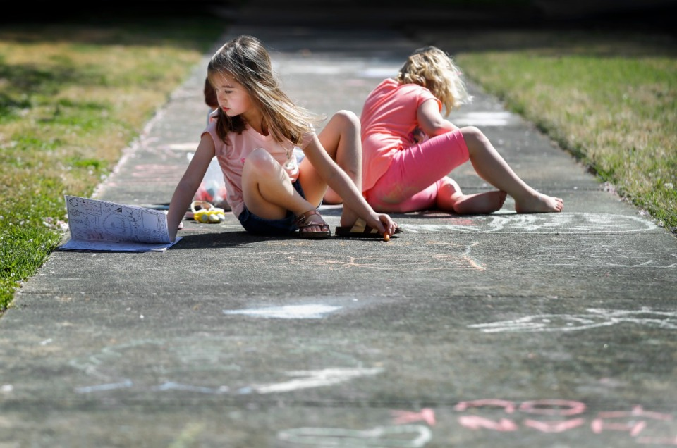 <strong>Elliana Mohundro, 7, (left) along with her friends draws encouraging messages to the sanitation workers and others walking along their street on Thursday, March 26, 2020 in East Memphis.</strong> (Mark Weber/Daily Memphian)