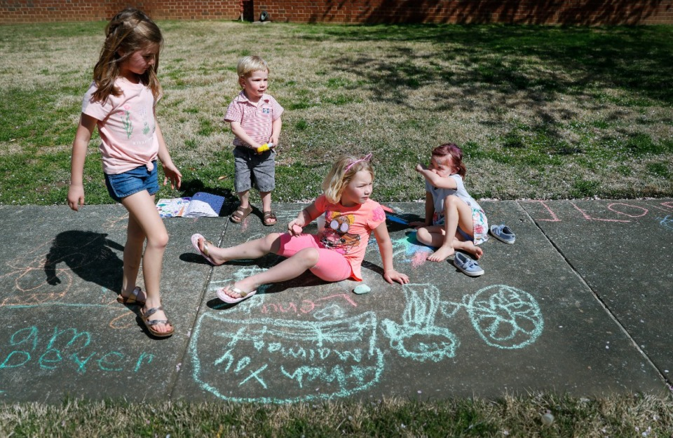 <strong>Neighborhood friends (let to right) Elliana Mohundro, 7, Lewis Koelsch, 3, Lena Koelsch, 6, and Namoi Burton, 4, draw encouraging messages to the sanitation workers and others walking along their street on Thursday, March 26, 2020 in East Memphis.</strong> (Mark Weber/Daily Memphian)