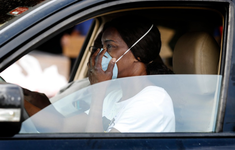 <strong>Gloria Snipes adjusts her facemask while getting a 14-day food box during the drive-thru event at Memphis Athletic Ministries' Grizzlies Center on Friday, March 27.</strong> (Mark Weber/Daily Memphian)