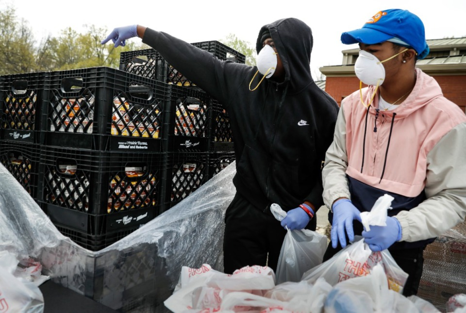 <strong>Cousins Zachary Lesueur, 14, (left) and LeDerion Upshaw, 15, grab cartons of milk as they assemble 14-day food boxes that were distributed at a drive-thru event on Friday, March 27.</strong> (Mark Weber/Daily Memphian)