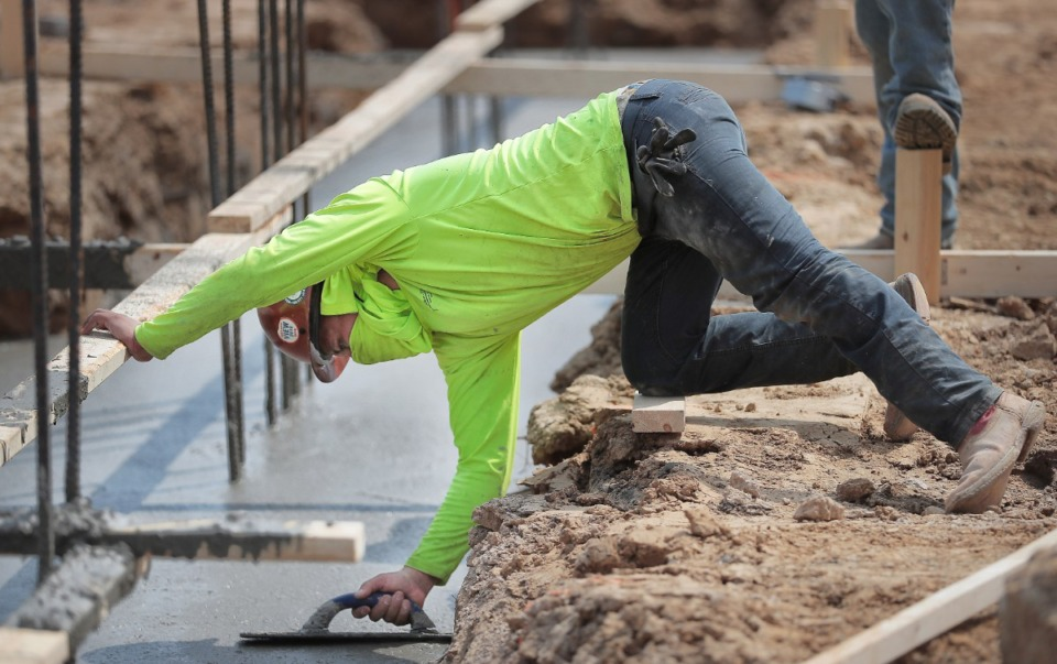 <strong>Basqualeto Pasqual smooths out fresh concrete as workers start pouring foundations on March 27, 2020, for the first buildings under construction at The Lake District, a 160-acre mixed-use project in Lakeland.</strong> (Jim Weber/Daily Memphian)