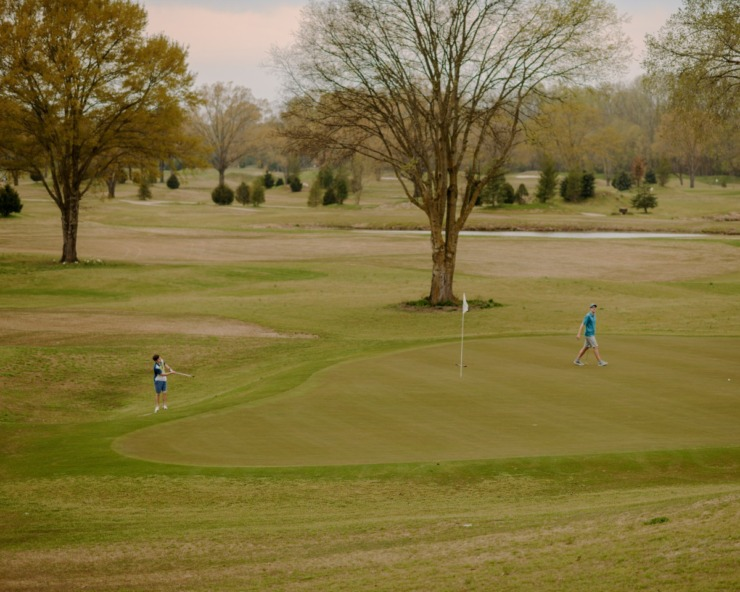 Two golfers at Mirimichi Golf Course chip onto the green on Friday, March 27, 2020. (Houston Cofield/Special to The Daily Memphian)