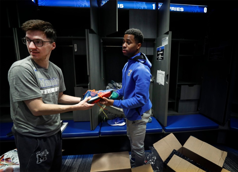 <strong>University of Memphis basketball student manager and equipment intern Sam McCadams (left) helps Tiger guard Tyler Harris pack up his locker on Friday, March 13, 2020, at the Laurie-Walton Family Practice Center.</strong> (Mark Weber/Daily Memphian)