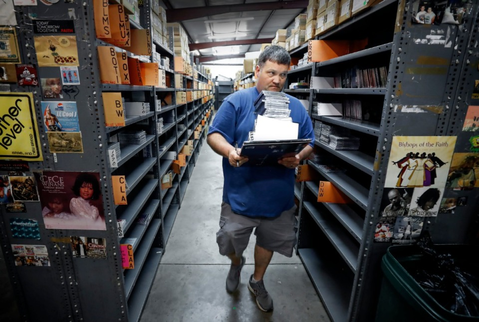 <strong>Select-O-Hits employee Chris Barker totes an order of cd&rsquo;s and vinyl records as he prepares a shipment at the independent music distribution company in Bartlett on Monday, March 16, 2020.</strong> (Mark Weber/Daily Memphian)