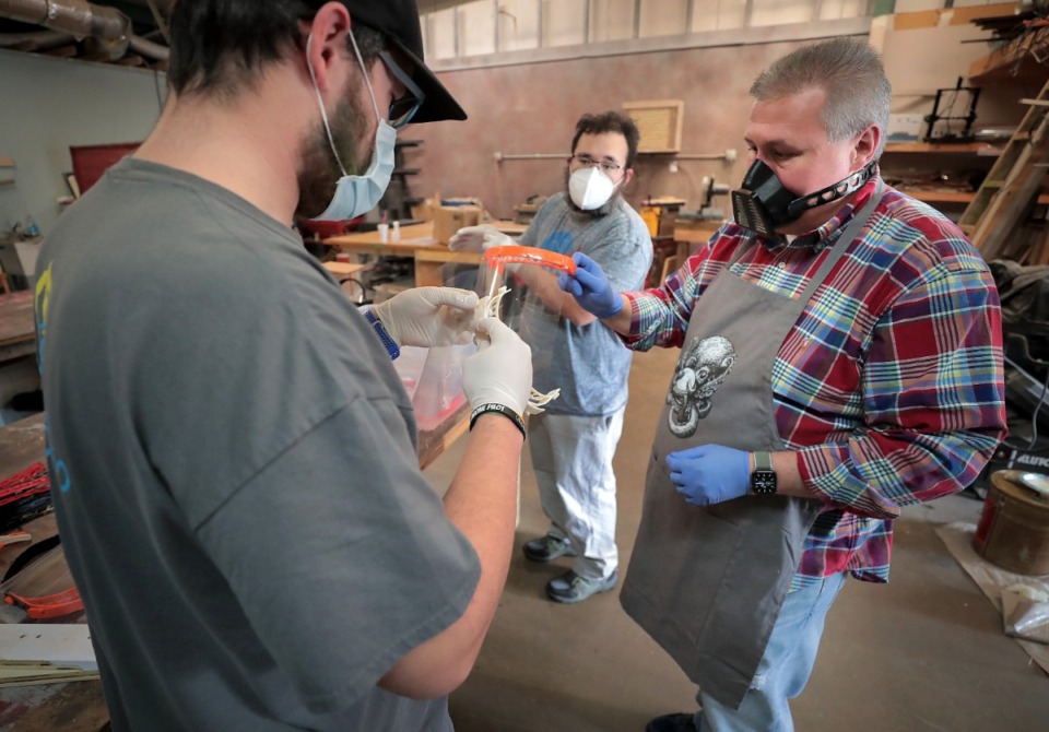 <strong>Dave Myers (left), Ernest McCracken and Rich Thompson (right) with the Midsouth Makers donate their time to assemble face shields for the Memphis Medical Society on March 29, 2020. The group of tinkerers used 3-D printers to create the frame and a laser cutter to make a matching transparent shield.</strong> (Jim Weber/Daily Memphian)