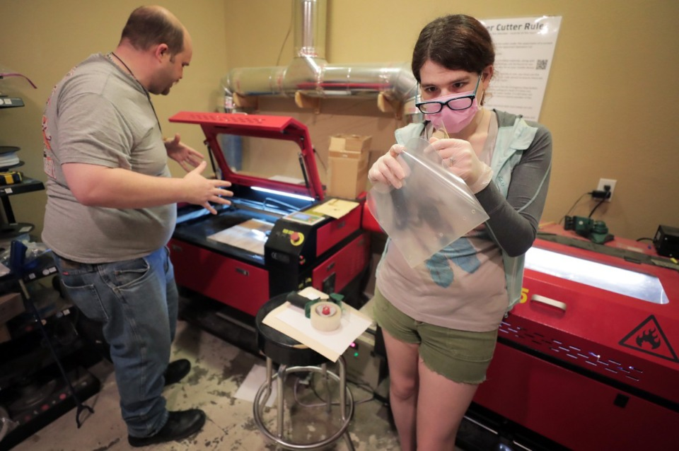 <strong>Renee Timbs (right) and Donngal Mac Ronain with the Midsouth Makers try to figure out the right settings to cut clear plastic without melting it while creating face shields for the Memphis Medical Society on March 29, 2020. The group of tinkerers used 3-D printers to create the frame and a laser cutter to make a matching transparent shield.</strong> (Jim Weber/Daily Memphian)