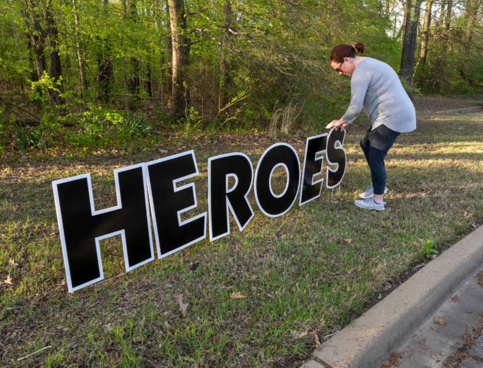 """<strong>Krystal Cruise places """"Heroes Work Here"""" sign outside Baptist Memorial Hospital-Collierville, Sunday, March 29, 2020. Citizens showed up at the parking lot Sunday night during shift change to show support to the health care workers.</strong> (Greg Campbell/Special to The Daily Memphian)"""