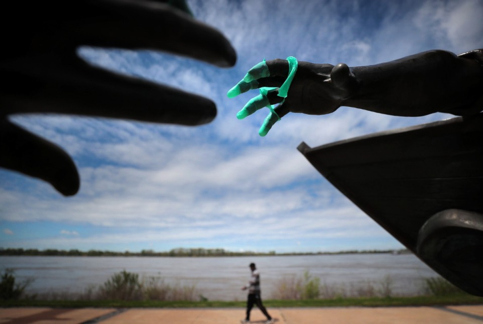 <strong>Davin Roberson passes by the Tom Lee statue with a tattered surgical glove while taking a morning walk through the sparsely populated Tom Lee Park on March, 31, 2020, after Memphis Mayor Jim Strickland announced that the city would start limiting access to city parks.</strong> (Jim Weber/Daily Memphian)