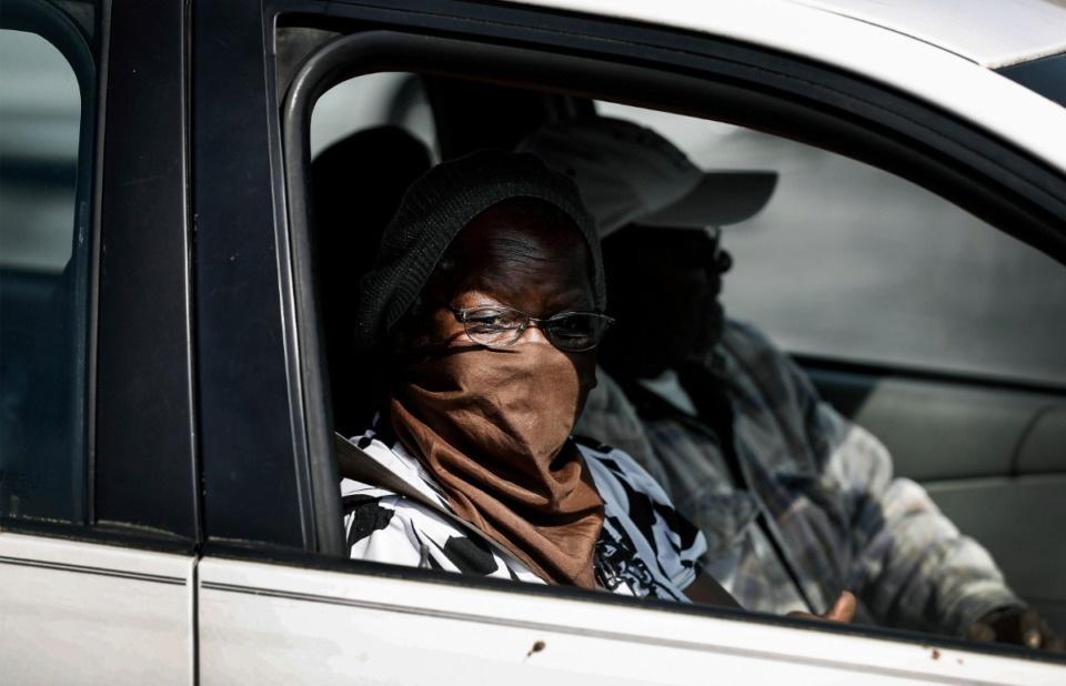 <strong>A women covers her face with a scarf while attending the Mid-South Food Bank mobile pantry event Wednesday, April 1, 2020 on E. Georgia Ave.</strong> (Mark Weber/ The Daily Memphian)