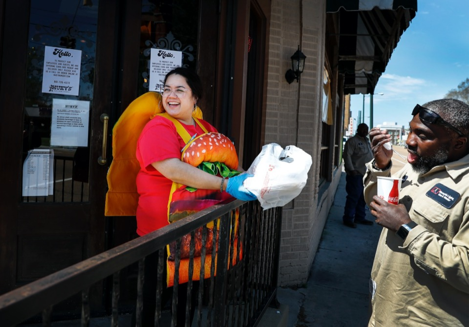 <strong>Huey's employee Jenna Cousino, wearing a a cheeseburger costume, delivers food to lunchtime customers on Thursday, April 2, 2020, at the Midtown Huey's location. Huey's has neither laid off any of their 565 employees nor cut employees' pay.</strong> (Mark Weber/Daily Memphian)