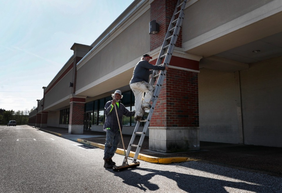 <strong>Roofers Larry Dennis (left) and Glenn Janes (right) descend a ladder after checking the roof of a vacant rental property in Gateway Shopping Center on Thursday, April 2. The U.S. Army Corps of Engineers will build a temporary hospital of non-acute beds at the shopping center to help deal with the expected coming surge in COVID-19 cases.</strong> (Mark Weber/Daily Memphian)