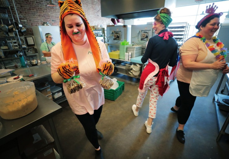 <strong>Jordan Badgett (left), Kat Gordon and Bridget Carratt joke around in the kitchen as the staff at Muddy's bake their way through the remainder of their supplies during a big temporarily-closing, April Fool's Day sale and costume party all rolled into one at the Muddy's Bakery on Broad Avenue on April 1, 2020.</strong>(Jim Weber/Daily Memphian)