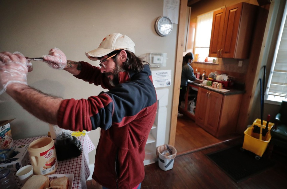 <strong>Constance Abbey community member Michael Smith tries to get the last bit of jam out of the jar while making PB&amp;J sandwiches for hungry homeless Memphians at the Downtown charity on April2, 2020.&nbsp;</strong>(Jim Weber/Daily Memphian)