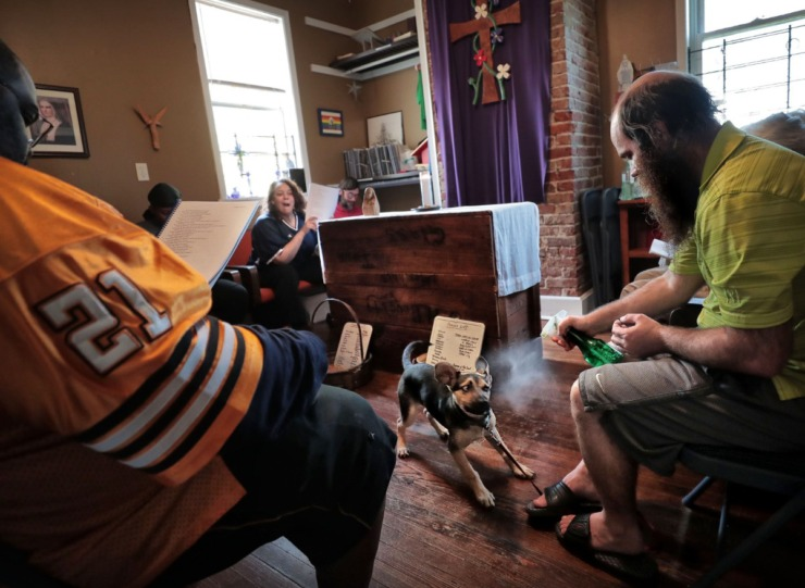 <strong>Constance Abbey community member Chris Murray (right) discourages his dog, Constance, from barking during the evening Bible service while Shamont Coon (left) reads scripture on April 2, 2020. Constance Abbey offers the Memphis homeless community food, laundry, showers and other services.</strong> (Jim Weber/Daily Memphian)