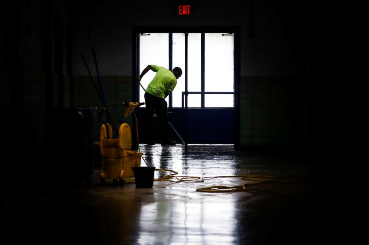 <strong>KIPP Memphis Collegiate High maintenance man Antoine Shotwell cleans floors at the school on Friday, April 3, 2020. Cleaning crews have worked to disinfect the school in anticipation that students will return to school at the end of the month. Due to the need for social distancing created by the coronavirus outbreak students have been competing the studies from home.</strong> (Mark Weber/Daily Memphian)
