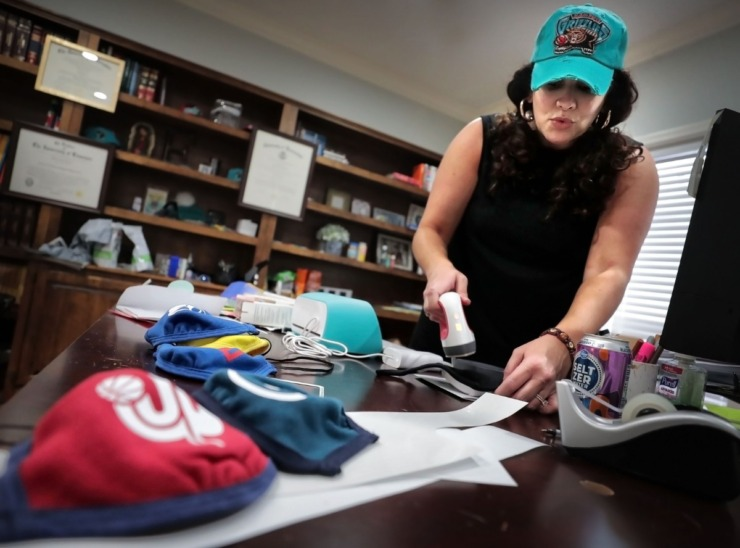 <strong>Rebecca Fava applies a logo to one of the cloth masks she has been decorating with Memphis themes and selling in her Southaven home office on April 3, 2020. Fava says she has a backlog of 50 masks, but has a shipment coming in from California to be adorned.</strong> (Jim Weber/Daily Memphian)