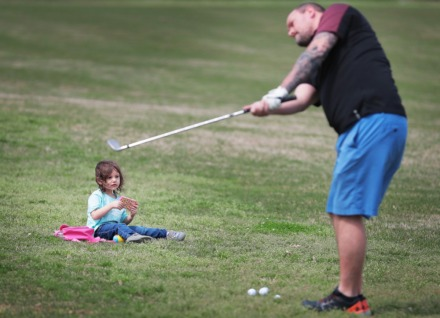 <strong>Leilani Ratts, 2, keeps herself entertained with video games while her father Andrew Ratts practices his chip shot at the Overton Park golf course on March 23, 2020.</strong> (Jim Weber/Daily Memphian)