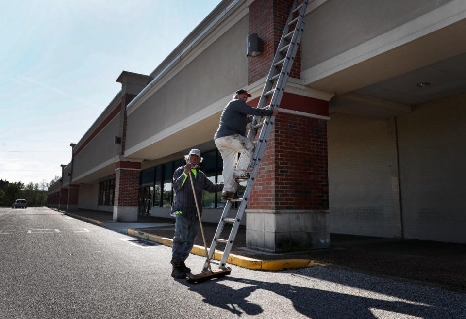 <strong>In anticipation of a coming surge in COVID-19 cases a shopping center on Jackson Avenue is being transformed into a hospital. Roofers Larry Dennis (left) and Glenn Janes (right) work on the roof at Gateway Center on Thursday, April 2, 2020. </strong>(Mark Weber/Daily Memphian)
