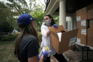 <strong>Stephanie Lepone takes a box of N95 masks from Jill Stockburger outside her East Memphis home April 6, 2020. Lepone, along with roughly 400 other volunteers agreed to help fix some nearly 20,000 masks Baptist Hospital found that were in need of new elastic straps.</strong> (Patrick Lantrip/Daily Memphian)