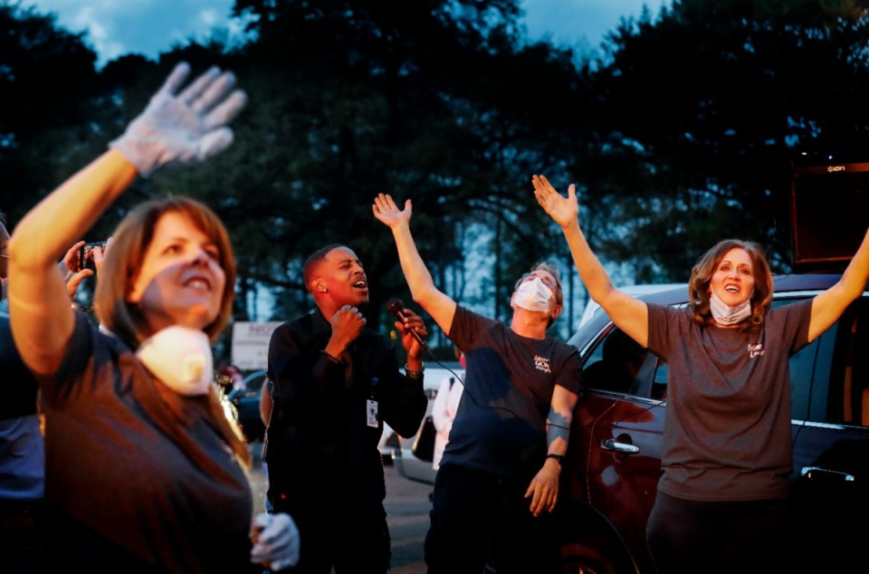 <strong>While St. Francis Hospital-Memphis staff member Daryl Moore (middle left) preaches, Julie Abell (left), Bill Wilson (middle right) and Vicki Wilson wave their hands during a prayer vigil for patients and staff in the parking lot on Monday, April 6, 2020.</strong> (Mark Weber/Daily Memphian)