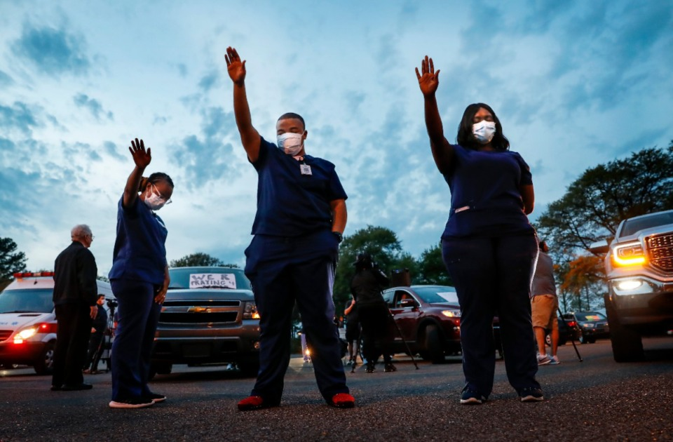 <strong>St. Francis Hospital-Memphis nurses, including Deonta Buck (middle) raise their hands in praise while attending a prayer vigil for patients and staff in the hospital parking lot on Monday, April 6, 2020.</strong> (Mark Weber/Daily Memphian)
