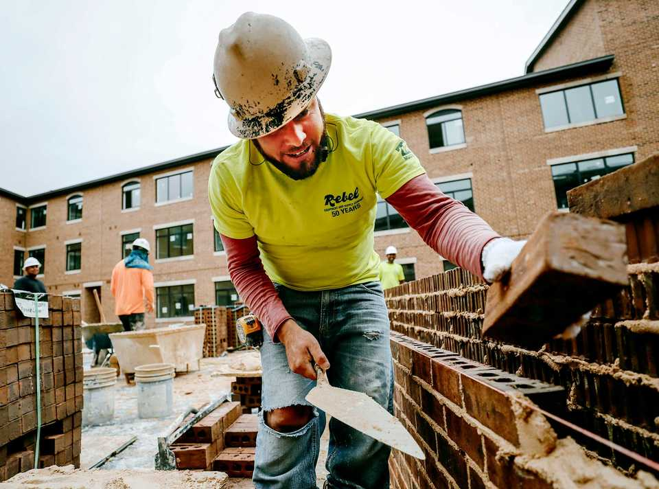 <strong>Gabriel Soriano, a Rebel Equipment and Supply employee, lays bricks in the courtyard of the new Thornwood apartments in Germantown. The apartment project is one of the four projects approved as part of the 18-month moratorium in Germantown and is expected to open at the beginning of 2019.</strong> (Houston Cofield/Daily Memphian)